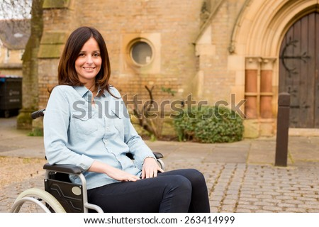 young woman in a wheelchair outside a church - stock photo