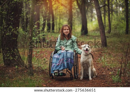Young woman in a wheelchair with the white seeing eye dog in spring forest - stock photo
