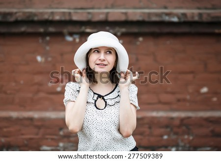 Young woman in a white blouse and hat posing on a blurred background old vintage brown brick wall. Model holds the edges of the hat by hand. Photo in retro style. - stock photo