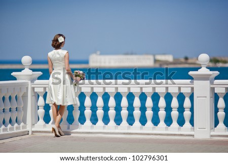 Young woman in a white dress looks at the sea - stock photo