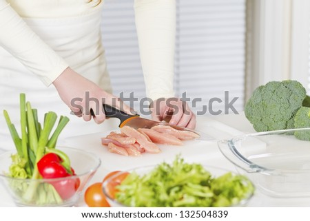Young woman in a white kitchen making a chicken meat fillet dish. - stock photo