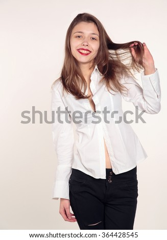 Young woman in a white shirt blouse on a light background. Young cheerful girl having fun. Happy smiling lady. - stock photo