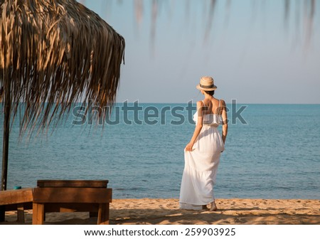 Young woman in a white sundress and hat  walking near the sea and looking into the distance - stock photo