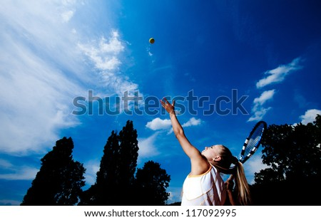 Young woman in a white tennis dress developing ball service - stock photo