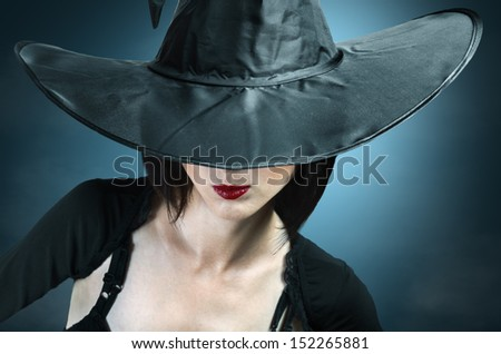 Young woman in a witch costume, her face covered with a hat - stock photo