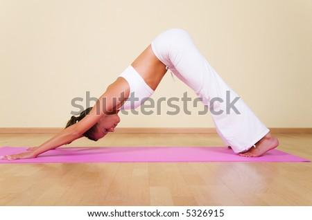 Young woman in a yoga position (Adho Mukha Svanasana) - stock photo