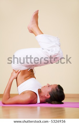 Young woman in a yoga position (Ardha Sarvangasana) - stock photo
