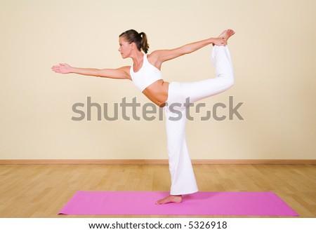 Young woman in a yoga position (Nataraja-asana) - stock photo