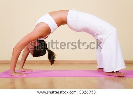Young woman in a yoga position (Urdhva Dhanurasana) - stock photo