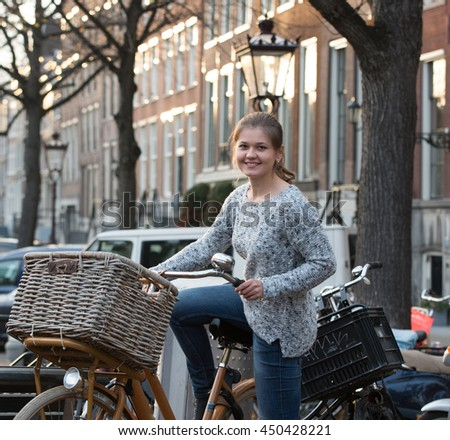 young woman in Amsterdam on bicycle with basket - stock photo