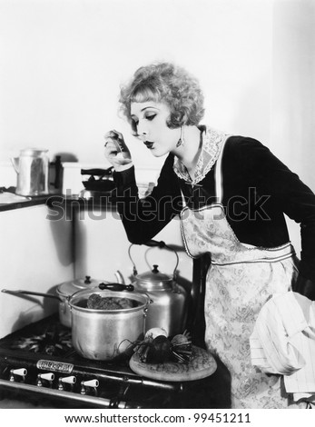 Young woman in an apron in her kitchen tasting her food from a pot - stock photo