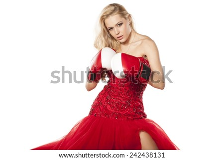 young woman in an elegant dress and boxing gloves