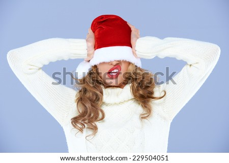Young woman in an oversized Santa hat which is covering her eyes pulling a funny face as she tries to wrest it off with her hands while celebrating Christmas - stock photo
