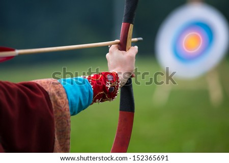 young woman in ancient clothes archery - stock photo