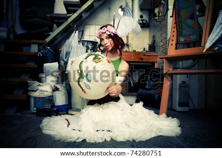 young woman in artistic studio sit on floor holding chinese lampion - stock photo