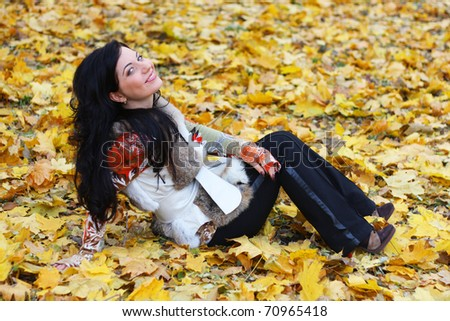 Young woman in autumn orange leaves