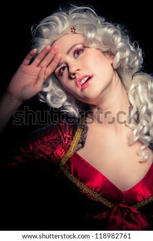 Young woman in baroque costume against dark background