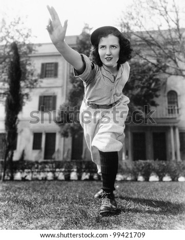 Young woman in baseball uniform throwing a ball - stock photo