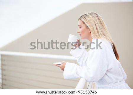young woman in bathrobe drinking coffee on balcony in the morning - stock photo