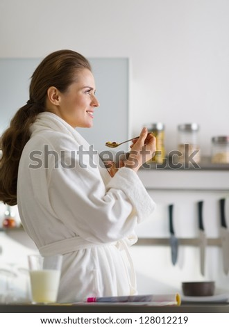 Young woman in bathrobe eating breakfast in morning - stock photo