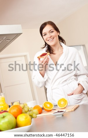Young woman in bathrobe eating toast for breakfast in kitchen