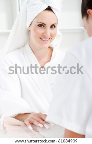 young woman in bathrobe in spa receiving manicure treatment
