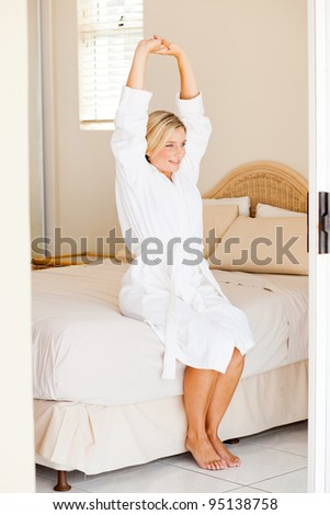 young woman in bathrobe sitting on bed and stretching
