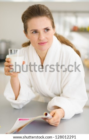 Young woman in bathrobe with milk and magazine - stock photo