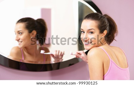 young woman in bathroom cleaning her teeth - stock photo