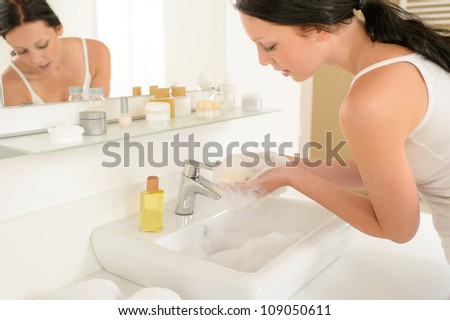 Young woman in bathroom washing her hands with soap bar - stock photo