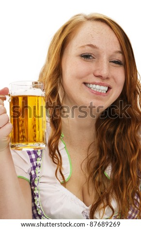 young woman in bavarian dress showing a glass with beer on white background - stock photo