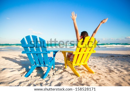 Young woman in beach chair raised her hands up - stock photo