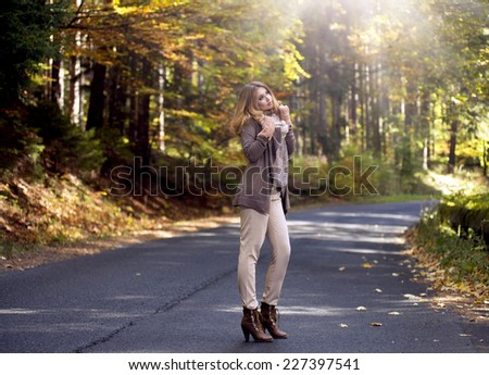 Young woman in beautiful autumn staying on street - stock photo