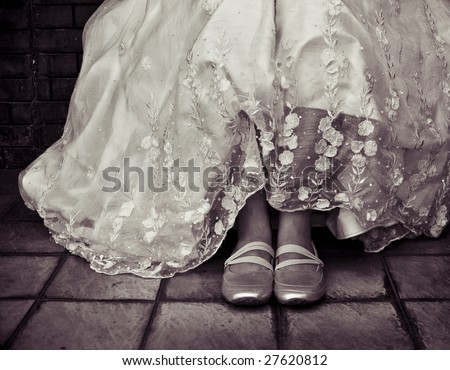 Young woman in beautiful wedding gown made with pineapple fiber. Casual sporty shoes are being worn on her feet. Vintage processing. - stock photo