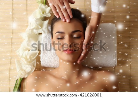 Young woman in beauty spa salon enjoying head massage with snow effect - stock photo