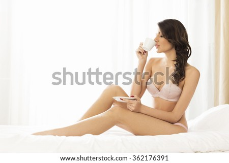 Young woman in bed drinking coffee