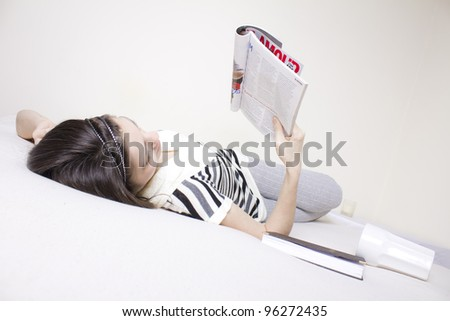 Young woman in bed rearding a fashion magazine - stock photo