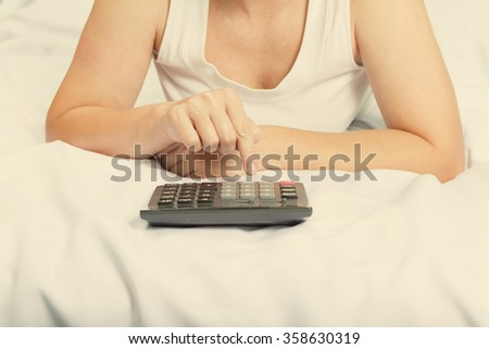 Young woman in bed with a calculator. Family budget. Credit, mortgage. - stock photo