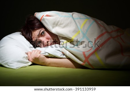 Young woman in bed with eyes opened suffering insomnia. Sleeping concept and nightmare issues