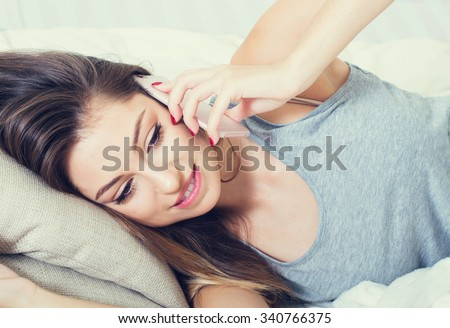Young woman in bedroom with mobile phone in bedroom