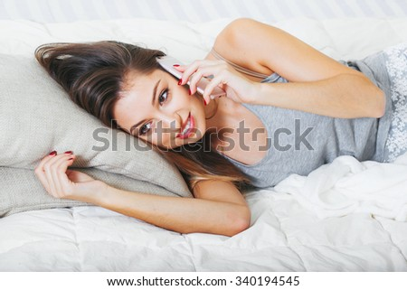 Young woman in bedroom with mobile phone portrait