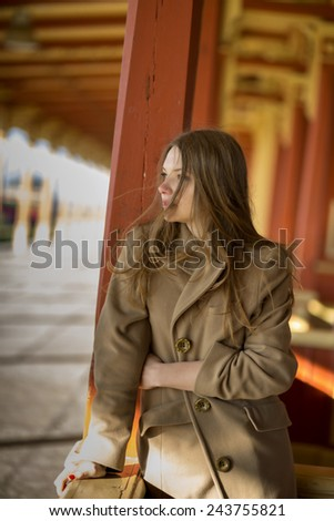 Young woman in beige coat sees coming train - stock photo