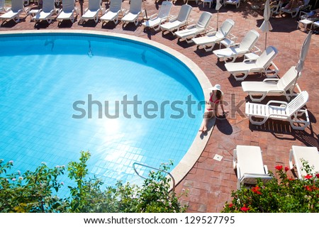 Young woman in big hat relaxing near the pool