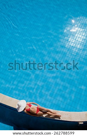 Young woman in big hat relaxing near the pool - stock photo