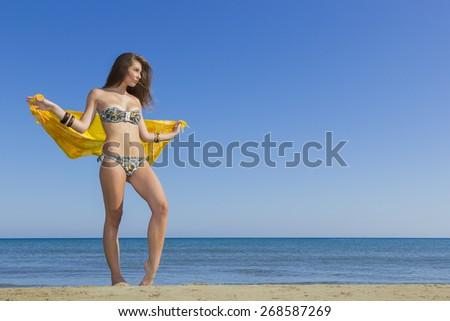 Young woman in bikini holding a yellow sarong on windy beach - stock photo
