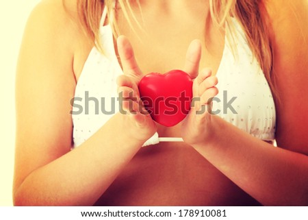 Young woman in bikini holding heart in her hands - stock photo
