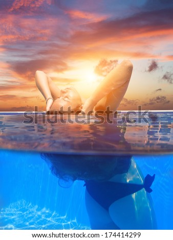 Young woman in bikini in the swimming pool at sunset - stock photo