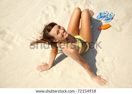 young woman in bikini sit and sunning on the beach under the bright sun - stock photo