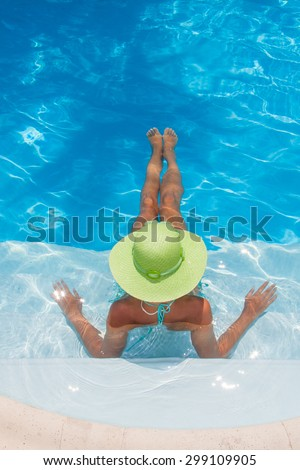Young woman in bikini wearing a straw hat by the swimming pool