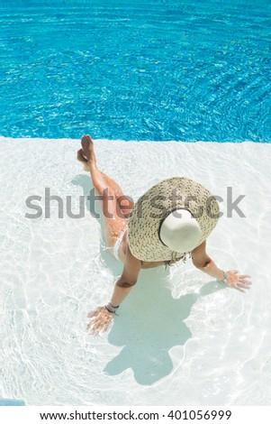 Young woman in bikini wearing a straw hat by the swimming pool - stock photo